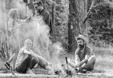 加入夏天野餐 见面在篝火附近的朋友停留和准备烤香肠快餐自然背景 库存图片