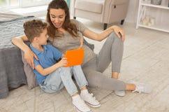 加入她的儿子观看的动画片的怀孕的母亲 免版税库存图片