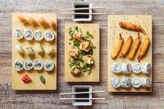 加利福尼亚寿司卷、缘故寿司卷、炸虾、gyozas和酱油在一张木桌上 库存照片