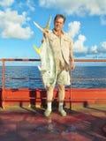 加勒比海,墨西哥- 2015年6月25日:人在海洋拿着一条大金枪鱼被抓从船在晴朗的夏日 免版税库存照片
