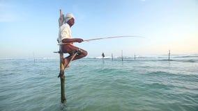 加勒,斯里兰卡- 2014年3月:结尾杆的老渔夫在海洋在加勒 高跷渔是仅的传统 股票视频