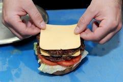 加在汉堡的厨师乳酪 准备和做汉堡包 库存照片