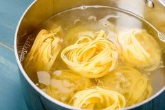 加在煮沸热水罐的Tagliatelle面团 库存照片