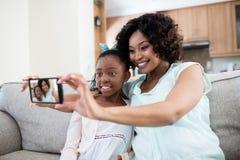 添加在活动房屋的母亲和女儿selfie在客厅 库存照片
