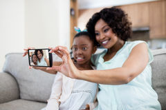 添加在活动房屋的母亲和女儿selfie在客厅 免版税图库摄影
