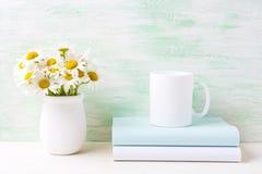加奶咖啡与白色领域春黄菊花束的杯子大模型在ha 免版税库存照片