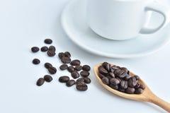 加奶咖啡杯子和咖啡豆在木匙子和在白色b 免版税库存照片