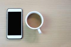 加奶咖啡杯子和智能手机黑屏在一棕色woode的 免版税库存照片