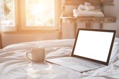 加奶咖啡杯子和膝上型计算机在床上在早晨时间与软性 免版税库存照片