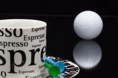 加奶咖啡杯子和高尔夫球 免版税库存照片