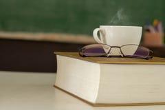 加奶咖啡杯子在书被安置 免版税图库摄影