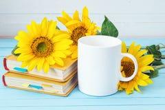 加奶咖啡杯子用向日葵和黄皮书在蓝色木 库存图片