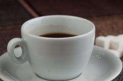 加奶咖啡杯子糖立方体和金属匙子在桌上 r 库存图片