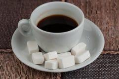 加奶咖啡杯子糖立方体和金属匙子在桌上 r 免版税图库摄影