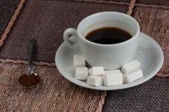 加奶咖啡杯子糖立方体和金属匙子在桌上 r 免版税库存照片