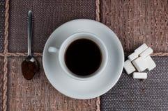加奶咖啡杯子糖立方体和金属匙子在桌上 r 图库摄影