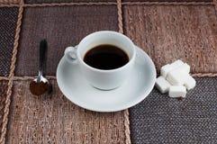 加奶咖啡杯子糖立方体和金属匙子在桌上 r 免版税库存图片