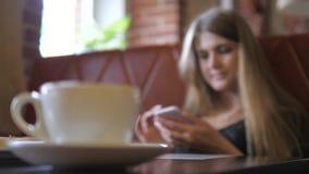 从加奶咖啡杯的转移焦点在有电话的少妇 股票视频