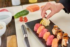 加姜的厨师到在板材的寿司 免版税库存照片