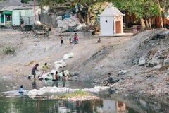 """加尔各答,印度†""""4月12日:可怜的印地安孩子工作在排序垃圾旁边在腐败的河 免版税库存照片"""