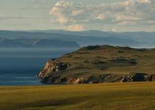 贝加尔湖与山和云彩的绿色风景 免版税图库摄影