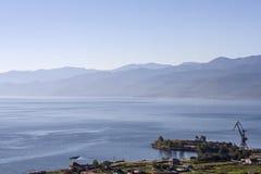 贝加尔湖岸的村庄在山的夏天在与木房子和crain的一个清楚的晴天 库存图片