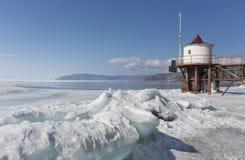 贝加尔湖岸的透明蓝色冰小丘 西伯利亚冬天与灯塔的风景视图 积雪的冰  免版税库存照片