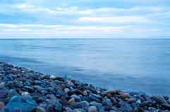 贝加尔湖石岸有云彩天空背景 库存图片
