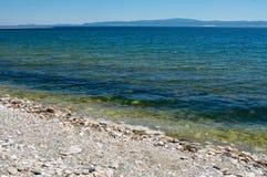 贝加尔湖蓝天背景石岸  免版税库存照片