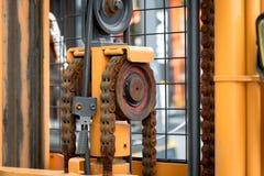 加工与嵌齿轮叉架起货车的轮子零件的引擎链子 免版税图库摄影