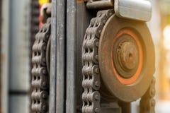加工与嵌齿轮叉架起货车的轮子零件的引擎链子 免版税库存图片