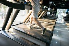 加工有人连续特写镜头的踏车在健身健身房 免版税库存图片