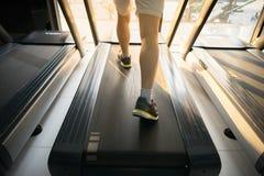 加工有人连续特写镜头的踏车在健身健身房 免版税库存照片