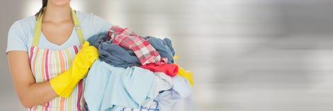 更加干净的举行的洗衣篮有明亮的背景 库存图片