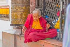 加德满都,尼泊尔2017年10月15日:关闭坐在户外和修士佩带的典型的衣裳的未认出的人  库存照片