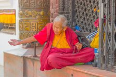 加德满都,尼泊尔2017年10月15日:关闭坐在户外和修士佩带的典型的衣裳的未认出的人  库存图片