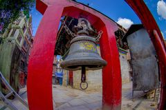 加德满都,尼泊尔2017年10月15日:关闭巨大的响铃在一个扔石头的金结构下在加德满都Boudhanath Stupa  免版税图库摄影