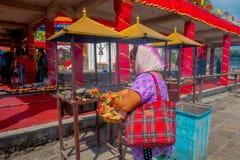 加德满都,尼泊尔- 2017年9月04日:关闭未认出的妇女在户外举行在篮子里面的供奉 免版税库存图片