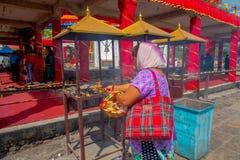 加德满都,尼泊尔- 2017年9月04日:关闭未认出的妇女在户外举行在篮子里面的供奉 图库摄影
