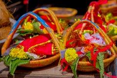 加德满都,尼泊尔- 2017年9月04日:关闭食物、果子和花的供奉在篮子里面在户外 免版税库存图片
