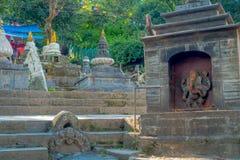 加德满都,尼泊尔2017年10月15日:在一个扔石头的结构的被雕刻的大象接近在Swayambhu奈斯寺庙的小stupas 库存图片
