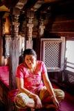 加德满都,尼泊尔- 2016年11月03日:坐在有被雕刻的窗口的一个房子里面的一名亚裔妇女的画象在Patan Durbar广场 库存照片