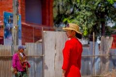加德满都,尼泊尔2017年10月15日:戴一件红色礼服和一个帽子有太阳镜的未认出的尼泊尔妇女在她的头 库存图片