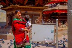 加德满都,尼泊尔2017年10月15日:穿典型的衣裳和运载她的胳膊的未认出的尼泊尔妇女一个婴孩 库存照片