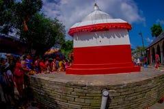 加德满都,尼泊尔- 2017年9月04日:给供奉的未认出的人民一个扔石头的白色和红色结构雕象 免版税库存照片