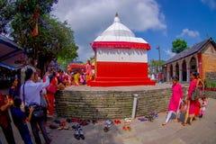 加德满都,尼泊尔- 2017年9月04日:给供奉的未认出的人民一个扔石头的白色和红色结构雕象 库存图片