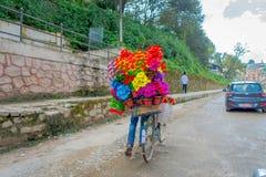 加德满都,尼泊尔2017年10月15日:装入在他的在一个罐的自行车塑料花的未认出的人,在街道 免版税库存照片