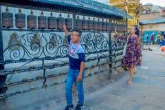 加德满都,尼泊尔2017年10月15日:走在接近尼泊尔宗教雕刻的户外的未认出的人民和 库存图片