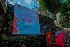 加德满都,尼泊尔- 2017年9月04日:走接近一个情报标志的早晨的未认出的妇女在 免版税库存照片