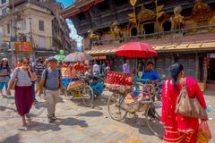 加德满都,尼泊尔2017年10月15日:走接近一辆自行车的未认出的人民用在金属里面的一些果子 库存照片